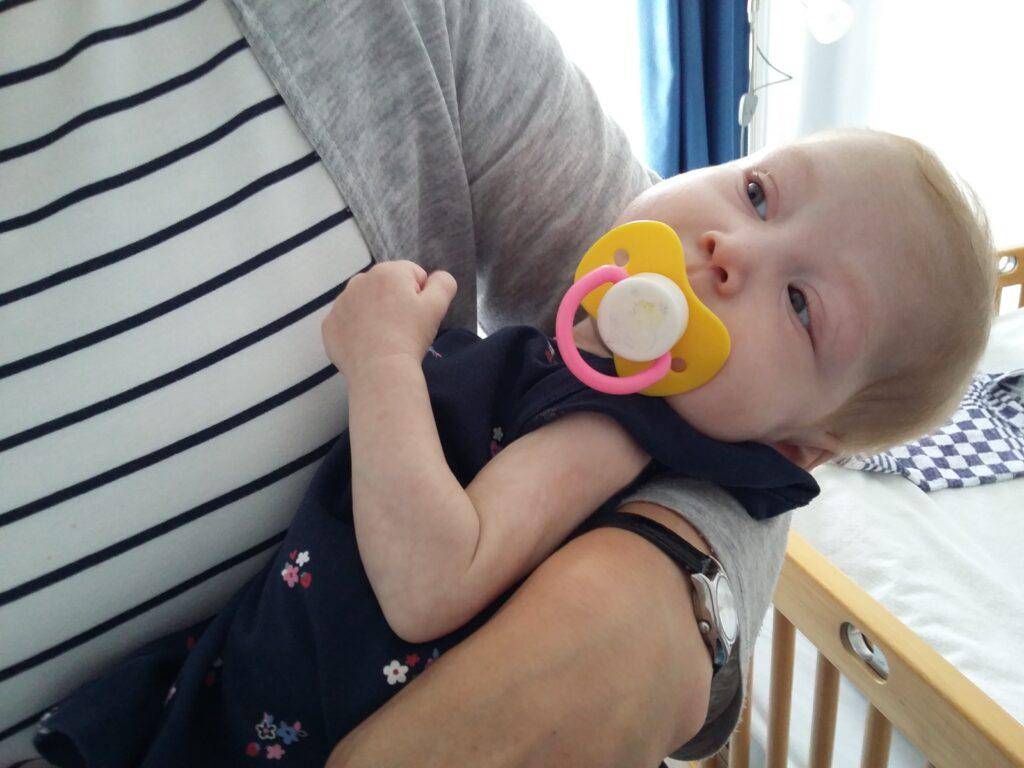 Kleines Kind mit gelbem Schnuller liegt im Arm einer Frau. Das Gesicht der Frau ist nicht zu sehen. Im Hintergrund sieht man ein Teil eines Kinderbettchens.